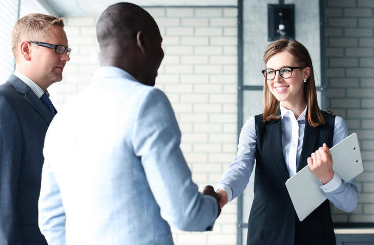 Smartly dressed woman shaking hands with man signifying training contract success via paralegal experience