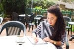 A young woman writing a law firm application outdoors with a coffee on the table.