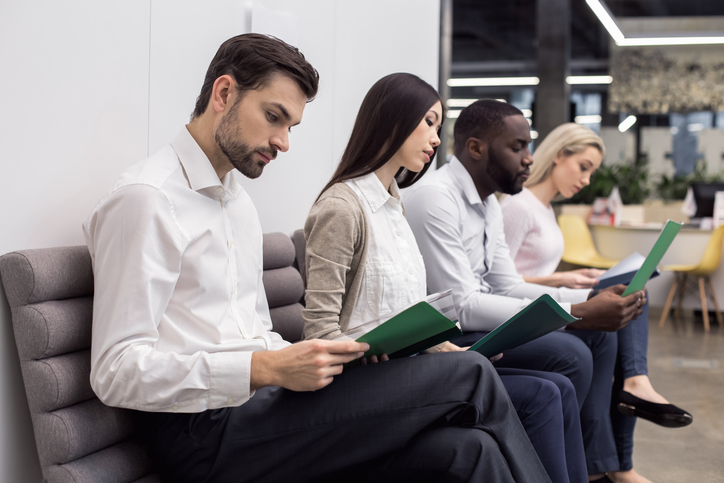 A row of young people sitting in an office with CVs for their training contract interview.