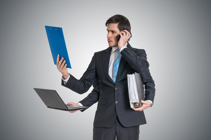 Multitasking man at work is calling with phone, reading report, working with laptop and holding office documents.