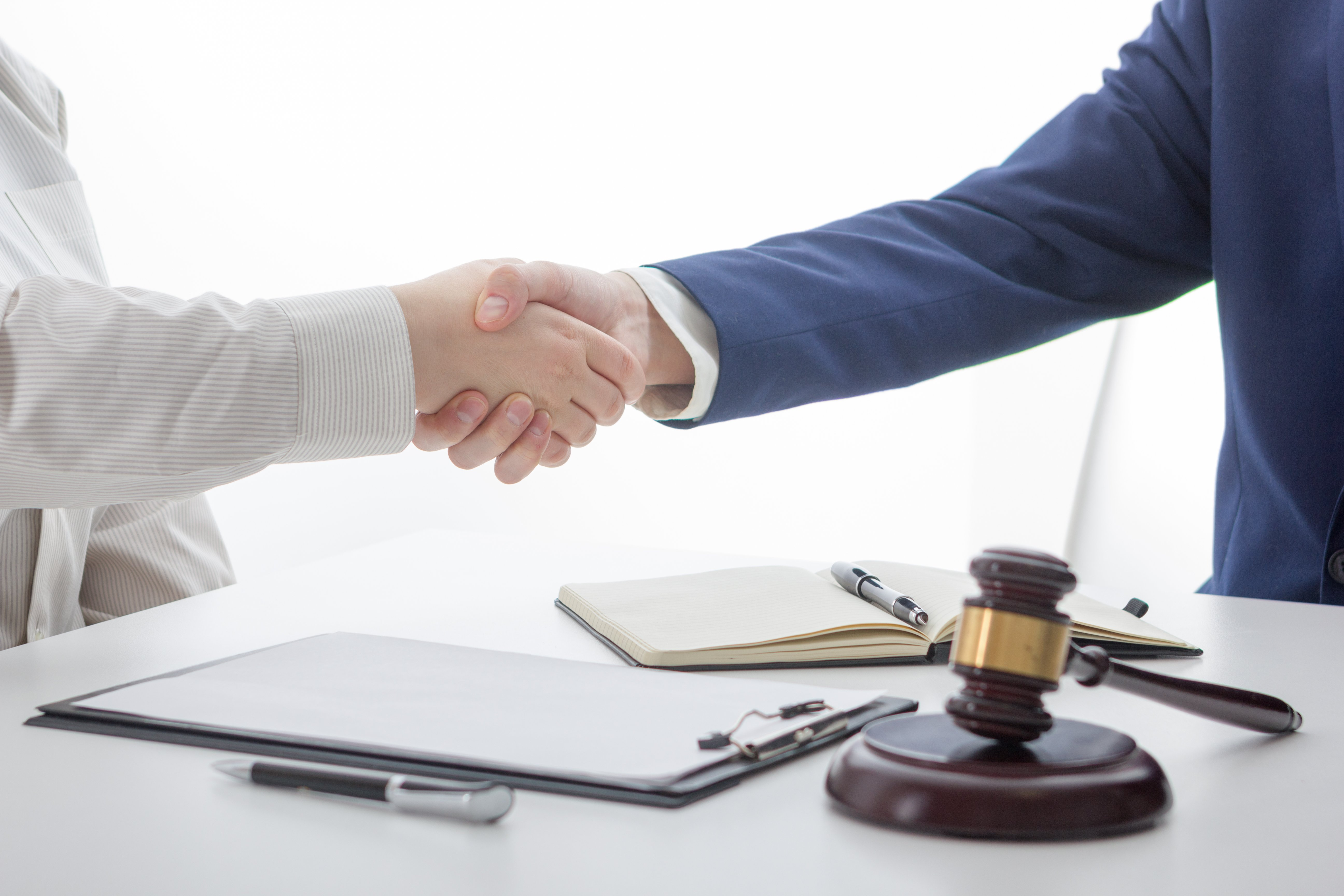 lawyers shaking hands at a law firm, suggesting the closing of a deal or acceptance of a training scheme