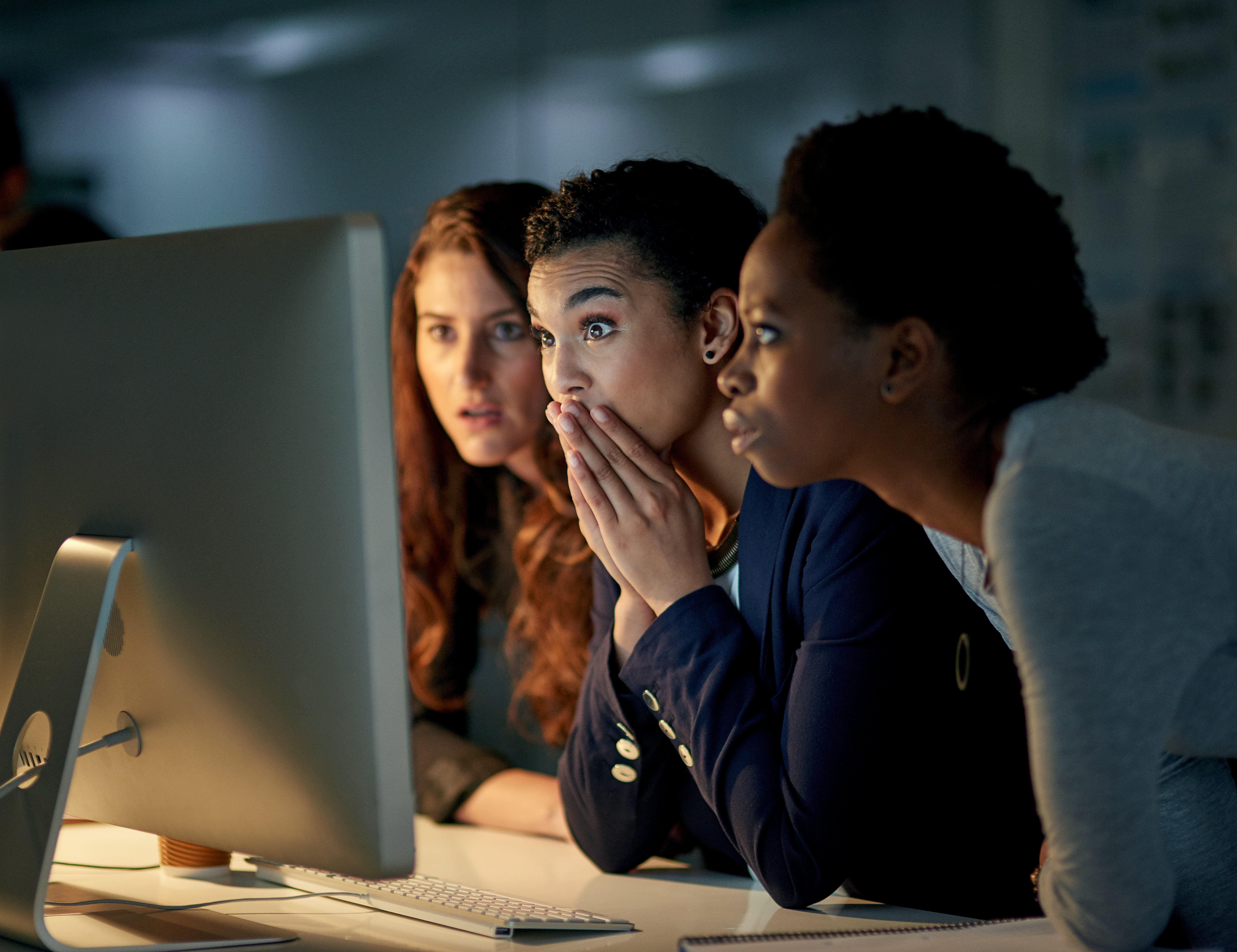 Three women stare at a desktop computer screen in a dark room and look shocked