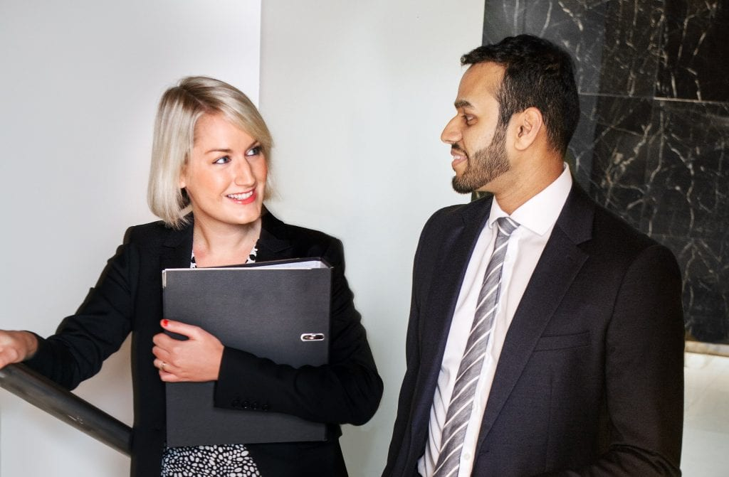 A man in a suit stands next to a woman in a smart black blazer who is holding a folder