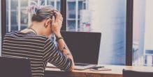 Upset woman with her head in her hands at a laptop