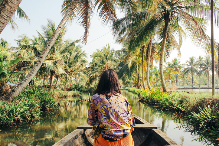 A young woman kayaks down a river surrounded by palm trees