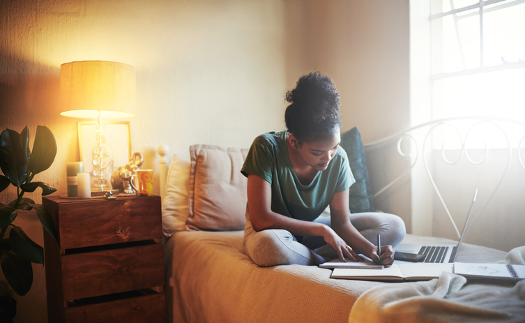 A woman sits on her bed and is studying