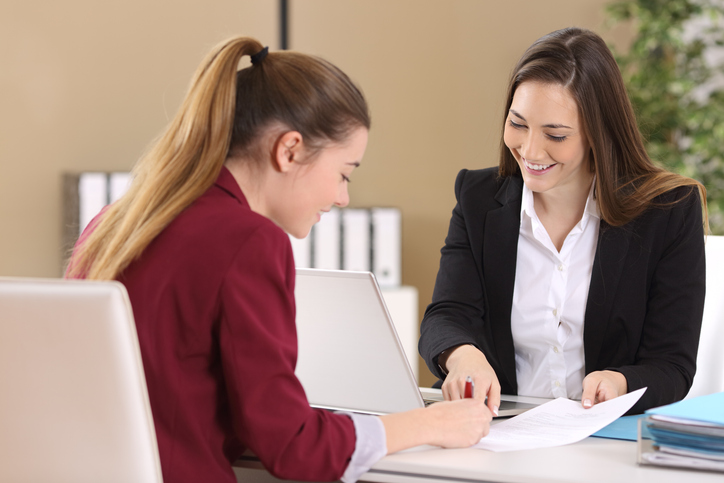 A woman sits at a desk with another woman and they look at a document on the table in front of them
