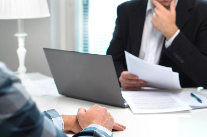 A person in a suit sits at a table with their laptop and paper surrounding them as they interview another person for a job