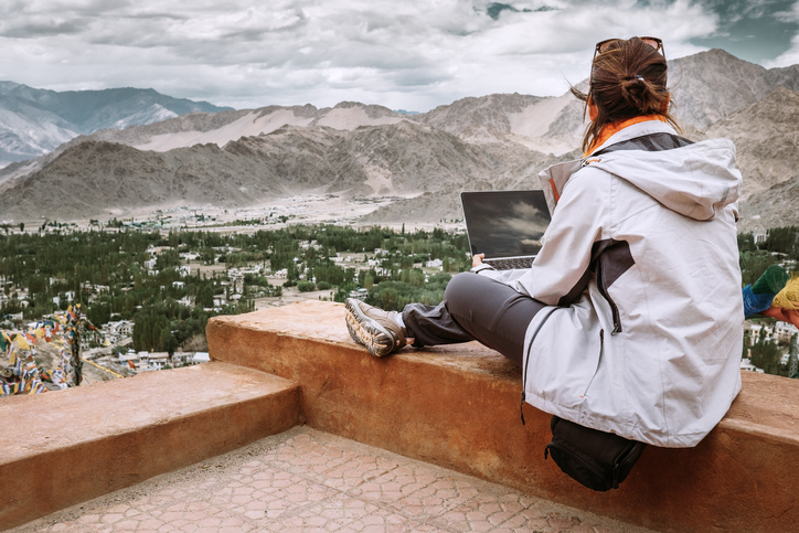 Girl on LLB law study abroad year holds laptop and looks at view