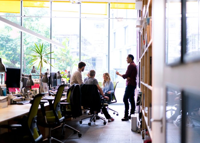 People sit and stand together in a light and airy office space