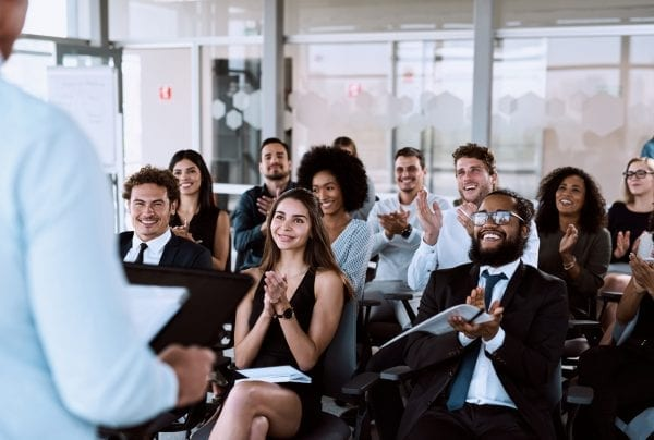 Group of young professionals seated in a conference room applauding a speaker who isn't in view