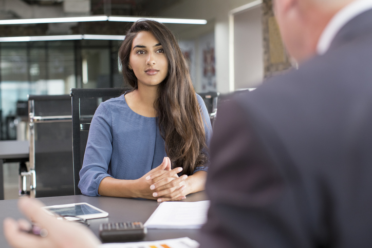 A woman is sat at a table interviewed by a man sitting opposite her